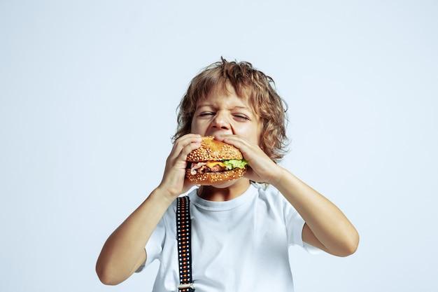 Vrij jonge krullende jongen in vrijetijdskleding op witte muur. hamburger eten. kaukasische mannelijke kleuter met heldere gezichtsemoties. jeugd, expressie, plezier maken, fast food. hongerig.
