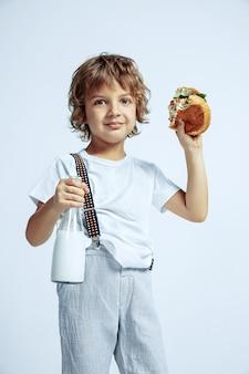 Vrij jonge krullende jongen in vrijetijdskleding op witte muur. hamburger eten met melkfles. kaukasische mannelijke kleuter met heldere gezichtsemoties. jeugd, expressie, plezier, fast food.