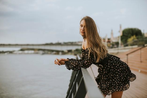 Vrij jonge lang haar donkerbruine vrouw die zich op de rivieroever bevindt