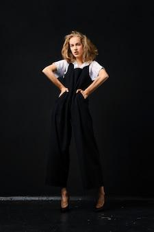 Vrij jonge mannequin in zwart broekpak en wit overhemd poseren over zwart