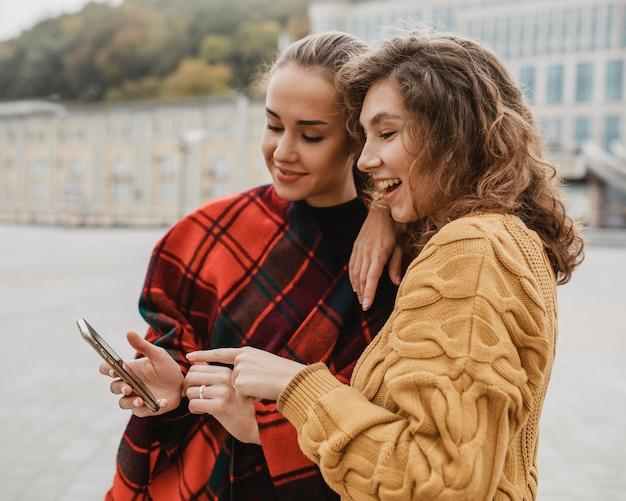 Vrij jonge meisjes die samen een telefoon controleren