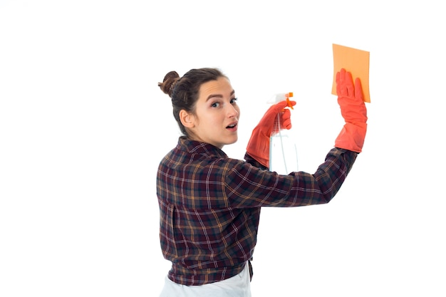 Vrij jonge meisjevrouw met reinigingsmiddelen die op witte muur worden geïsoleerd