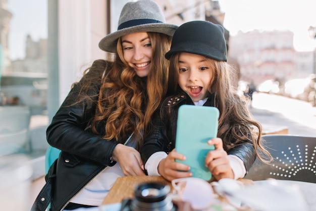 Vrij jonge moeder en haar schattige dochter die plezier hebben en selfies maken. meisje verrast in de telefoon kijken en glimlachen op de achtergrond van de zonnige stad. stijlvol gezin, echte emotie, goed humeur.
