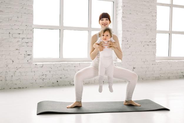 Vrij jonge moeder in witte sportkleding doet fysieke fitnessoefeningen plie squats op zwarte mat, samen met haar kleine babymeisje