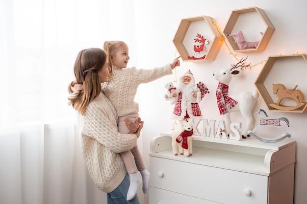 Vrij jonge moeder met haar schattige dochter in de buurt van de kerstboom binnenshuis