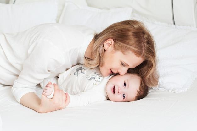 Vrij jonge moeder met haar zoontje in bed. grappige lachende ochtend. witte slaapkamer