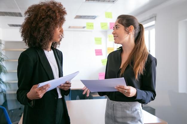Vrij jonge ondernemers bespreken projectplan en glimlachen. twee mooie vrouwelijke collega's documenten houden en praten in vergaderruimte. teamwork, bedrijfs- en managementconcept