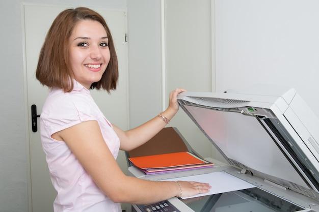Vrij jonge secretaresse die een kopieermachine met behulp van