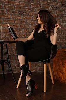 Vrij jonge sexy vrouw die met lang haar de wijnfles houdt