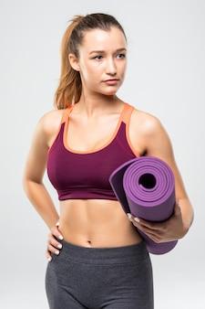 Vrij jonge sportvrouw die fitnessmat houdt terwijl geïsoleerd staat