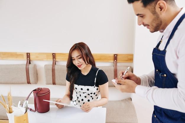 Vrij jonge vietnamese vrouw die menu leest en bestelling plaatst wanneer de ober het opschrijft