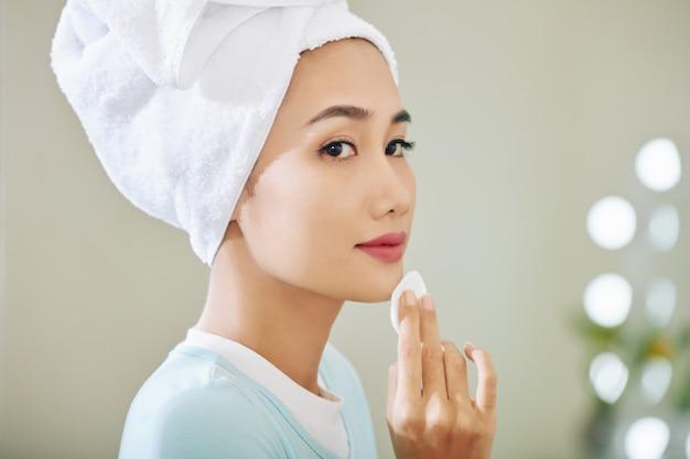 Vrij jonge vietnamese vrouw toner op haar huid toe te passen na het wassen van gezicht
