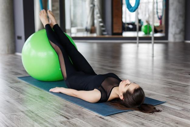 Vrij jonge vrouw die buikspieroefeningen op de groene bal in gymnastiek buigen