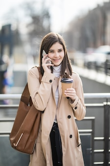 Vrij jonge vrouw die de de koffiekop en telefoon lopen van de straatholding