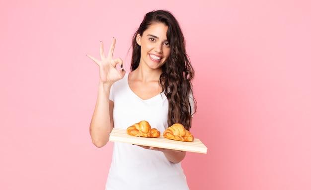 Vrij jonge vrouw die een croissantdienblad houdt