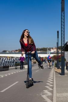 Vrij jonge vrouw die een elektrische autoped in de straat berijdt