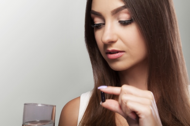 Vrij jonge vrouw die een zwarte pil neemt en een glas water houdt.