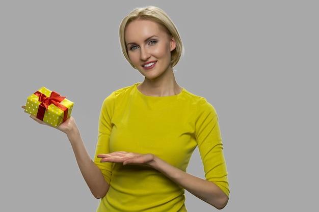 Vrij jonge vrouw die giftdoos toont. mooie vrouw bij het voorstellen van giftdoos op grijze achtergrond. bonus voor favoriete klanten.