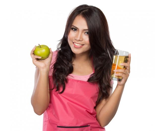 Vrij jonge vrouw die groen appel en sap houdt