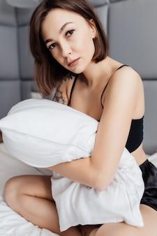 Vrij jonge vrouw die haar hoofdkussen in de ochtend in haar slaapkamer thuis omhelst
