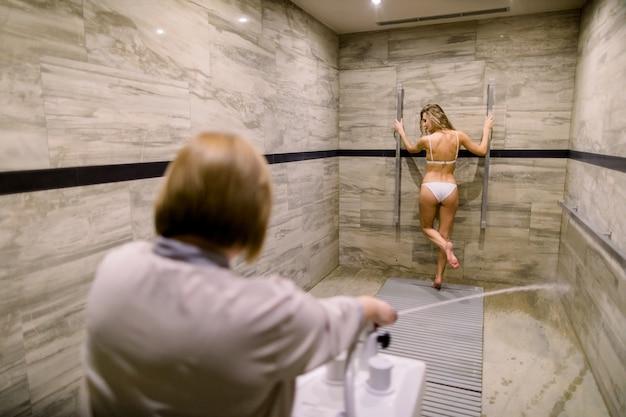 Vrij jonge vrouw die hogedrukmassage met sharko-douche in modern kuuroordcentrum hebben. vrouwentherapeut die de procedure van de kuuroorddouche voor vrouwelijke cliënt uitvoeren