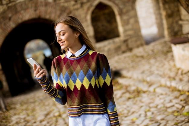 Vrij jonge vrouw die in de herfstpark loopt en een mobiele telefoon met behulp van