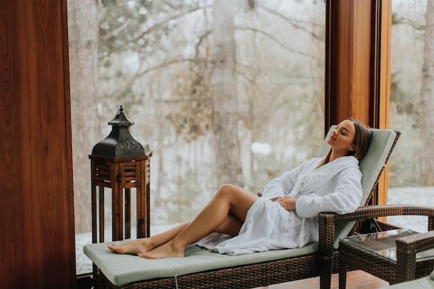 Vrij jonge vrouw die in deckchair door het binnen zwembad bij de winter ontspant