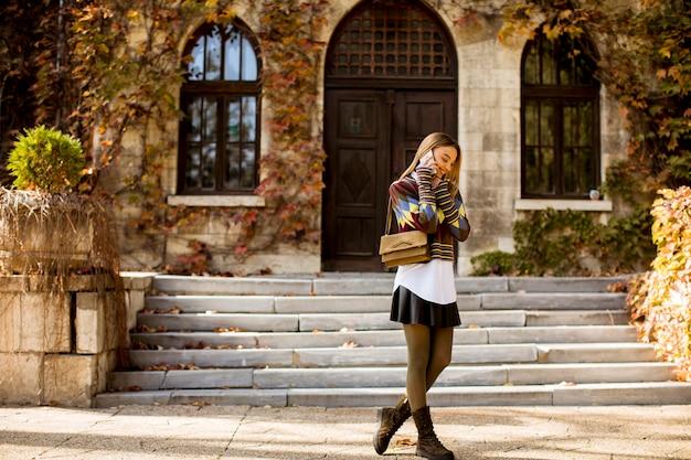 Vrij jonge vrouw die in het de herfstpark loopt