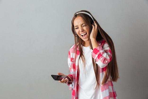 Vrij jonge vrouw die in hoofdtelefoons aan muziek en het zingen luistert