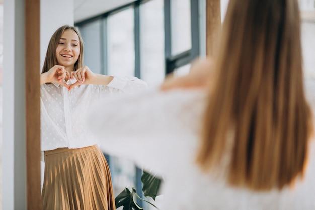 Vrij jonge vrouw die in toevallige uitrusting spiegel onderzoekt