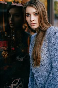 Vrij jonge vrouw die in venster wordt weerspiegeld.