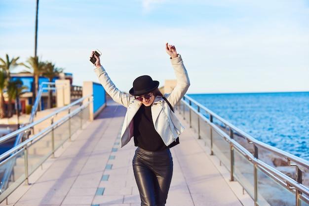 Vrij jonge vrouw die in zwarte hoed door het overzees loopt