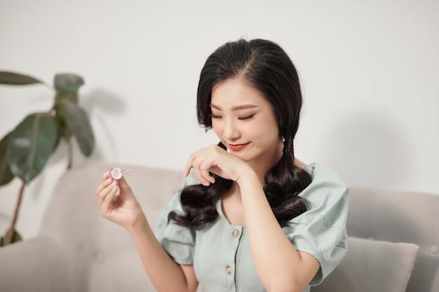 Vrij jonge vrouw die laat zien hoe hyaluronzuur eruitziet geïsoleerd. vrouw die anti-verouderingsproduct gebruikt.