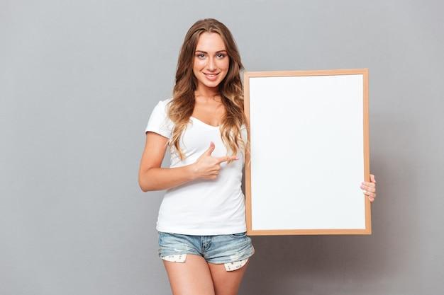 Vrij jonge vrouw die leeg leeg bord houdt dat op de grijze muur wordt geïsoleerd