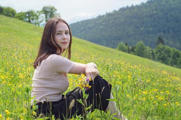Vrij jonge vrouw die met boeket van wilde bloemen op het gazon zit