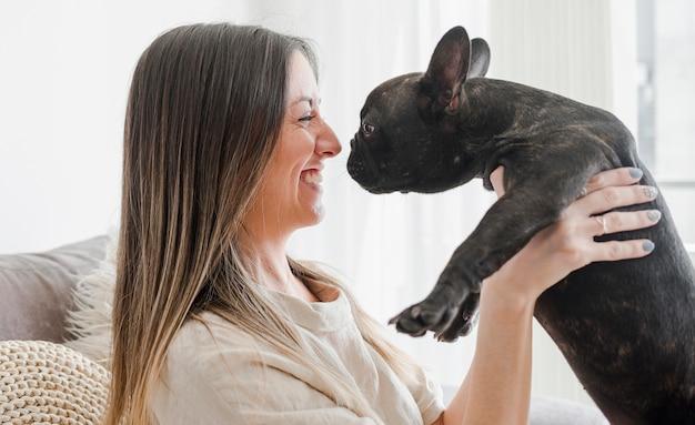 Vrij jonge vrouw die met haar puppy speelt