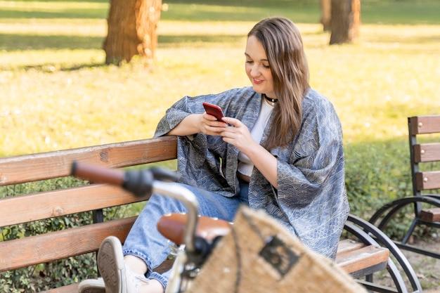 Vrij jonge vrouw die mobiele telefoon doorbladert