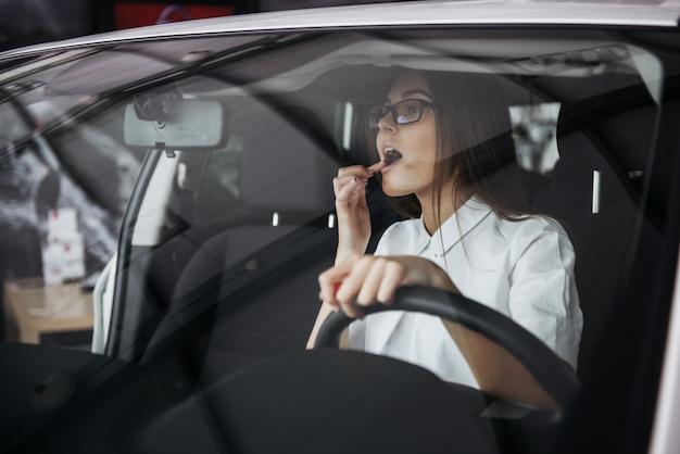 Vrij jonge vrouw die nieuwe auto drijft.