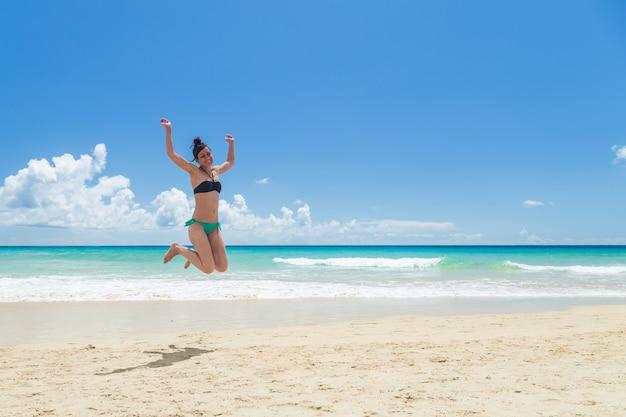 Vrij jonge vrouw, die op het strand geniet van