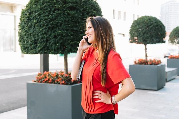Vrij jonge vrouw die op mobiele telefoon in stad spreekt