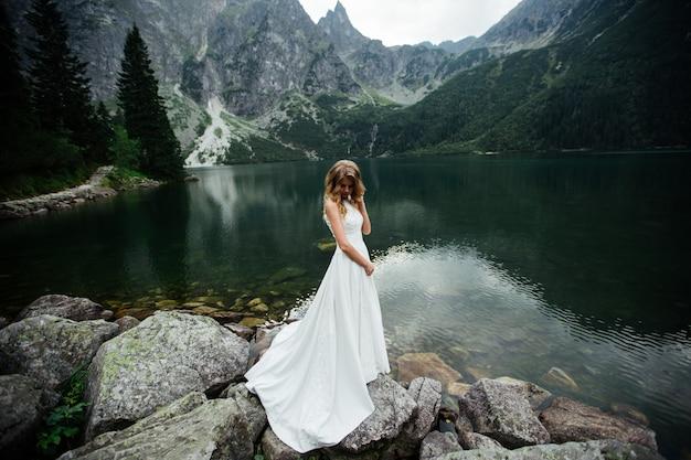 Vrij jonge vrouw die tijd in de bergen doorbrengen dichtbij het meer. de bruid komt naar boven.