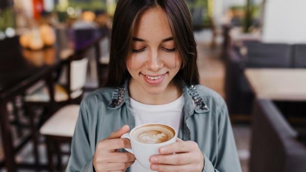 Vrij jonge vrouw die van een koffiekop geniet