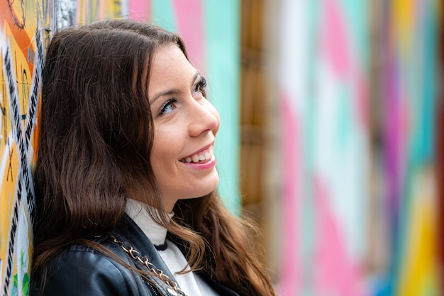 Vrij jonge vrouw die zich door muur bevindt die met graffiti wordt bespoten