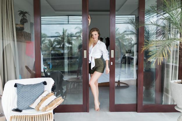 Vrij jonge vrouw die zich in de deuropening op het balkon bevindt en buiten in de tuin kijkt