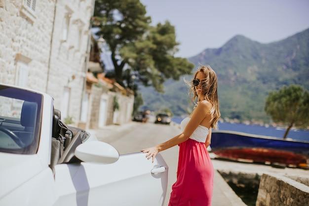 Vrij jonge vrouw door de witte cabriolet auto
