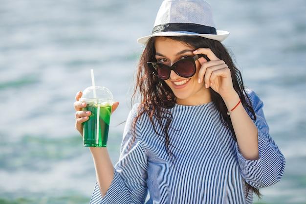 Vrij jonge vrouw het drinken cocktail op het strand. aantrekkelijk meisje dat een drank aanbiedt. mooie vrouw limonade drinken