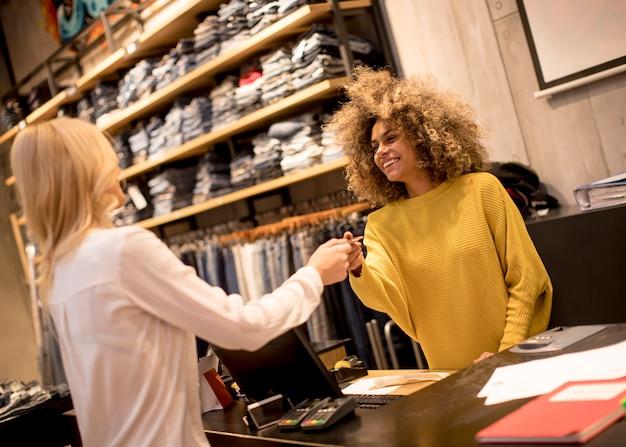 Vrij jonge vrouw het kopen kleren in manieropslag