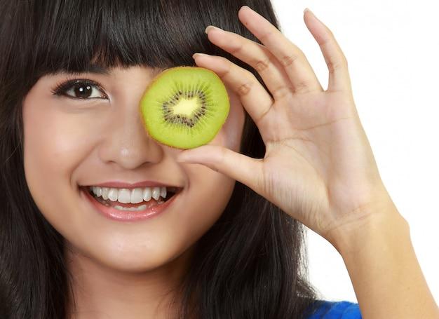 Vrij jonge vrouw houdt kiwi voor haar ogen