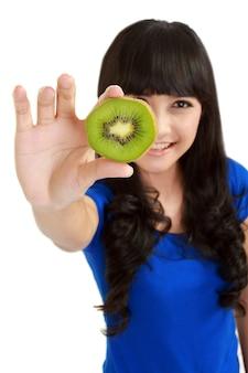 Vrij jonge vrouw houdt kiwi voor haar ogen Premium Foto