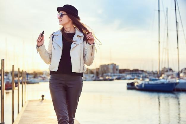 Vrij jonge vrouw in zwarte hoed met vape bij een zeehaven